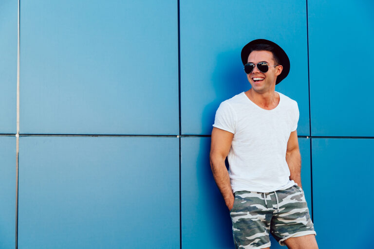 Young man in sunglasses standing on the blue wall background