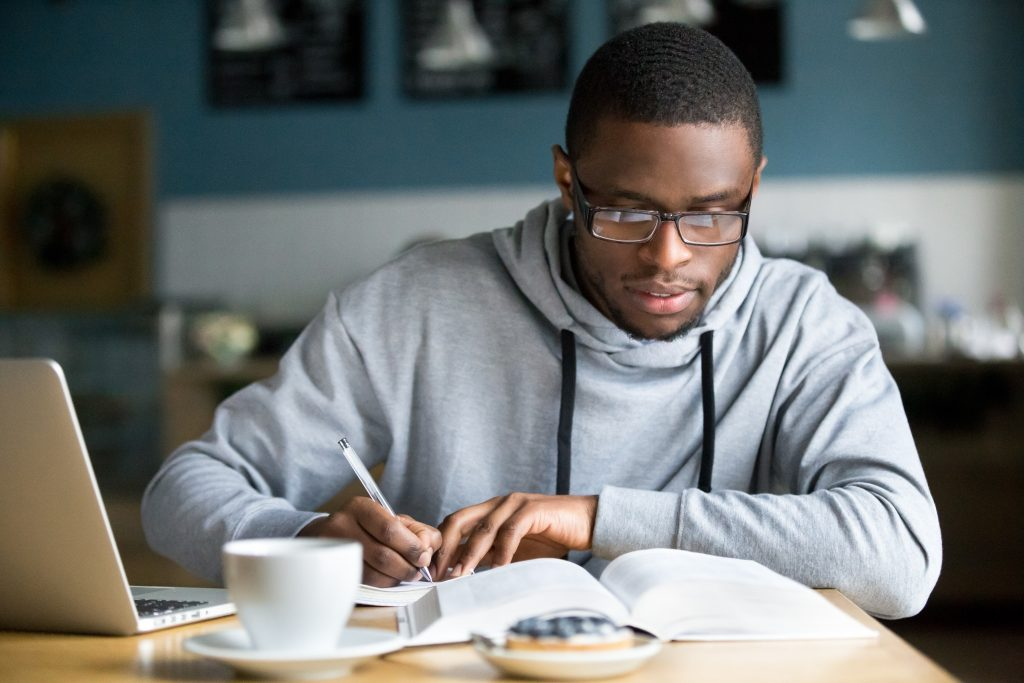 Man reading a book while taking notes and drinking coffee